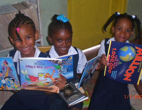 Children proudly display their new library books.