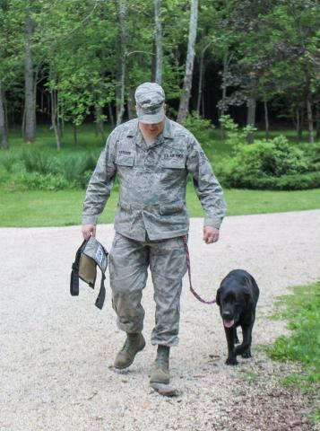 A service dog stands with his soldier.